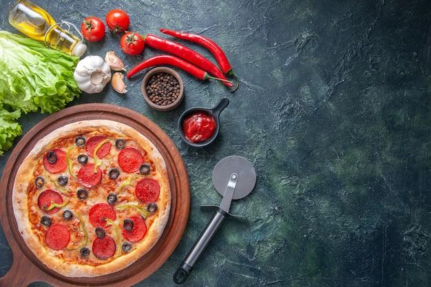 Deliziosa pizza fatta in casa su tavola di legno pomodori ketchup garlics pepe olio bottiglia verde fascio su superficie scura