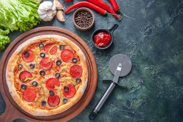 Deliziosa pizza fatta in casa su tavola di legno pomodori ketchup garlics pepe olio bottiglia fascio verde sul lato destro su superficie scura
