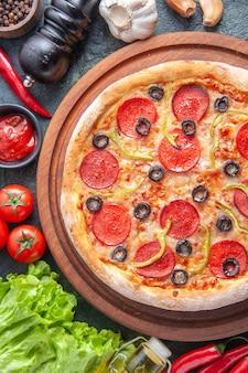 Deliziosa pizza fatta in casa su tagliere di legno pomodori ketchup all'aglio fascio verde su superficie scura