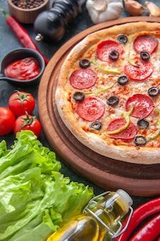 Deliziosa pizza fatta in casa su tagliere di legno pomodori ketchup aglio verde bottiglia di olio su superficie scura
