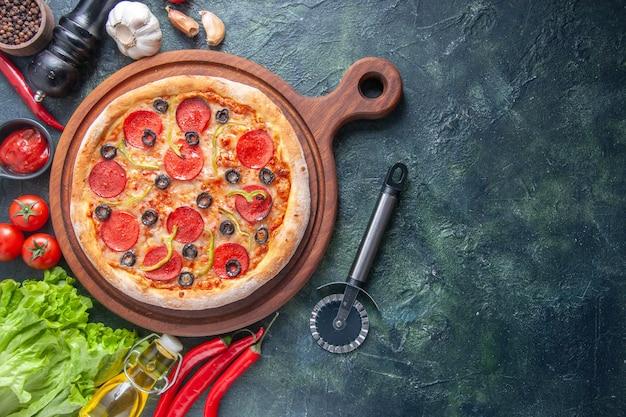 Deliziosa pizza fatta in casa su tagliere di legno pomodori aglio ketchup fascio verde bottiglia di olio pepe su superficie scura