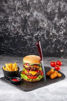 Deliziosi panini fatti in casa e pepite di pollo patatine ketchup forchetta su tavola nera pomodori con gambo su superficie grigia di ghiaccio