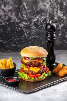 Deliziose patatine fritte fatte in casa con ketchup e panino su tavola nera su superficie grigia