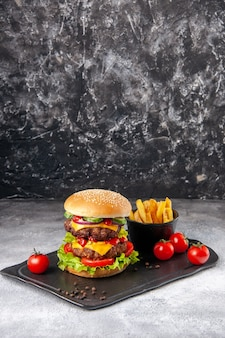Delizioso panino fatto in casa e patatine fritte ketchup su tavola nera su superficie di ghiaccio grigio con spazio libero free