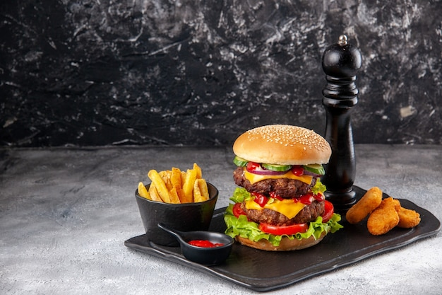 Deliziosi sandwich fatti in casa e patatine fritte ketchup bocconcini di pollo su tavola nera sul lato sinistro su superficie grigia