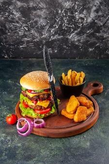 Deliziosi sandwich fatti in casa pomodori pepe su tagliere di legno cipolle pomodoro con gambo pepite di pollo patatine fritte forchetta su superficie di colore scuro