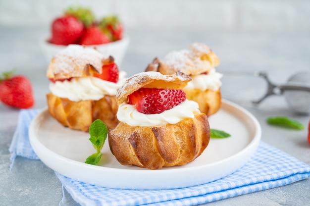 Deliziosi tortini fatti in casa profiterole di pasta choux con crema pasticcera alle fragole e polvere di glassa