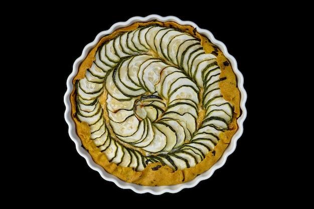 Quiche fatta in casa deliziosa di zucchine e formaggio su un piatto bianco. i pezzi di zucchine sono disposti a spirale