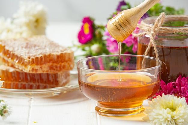 Delizioso miele con mestolo di miele in legno su superficie di legno bianca