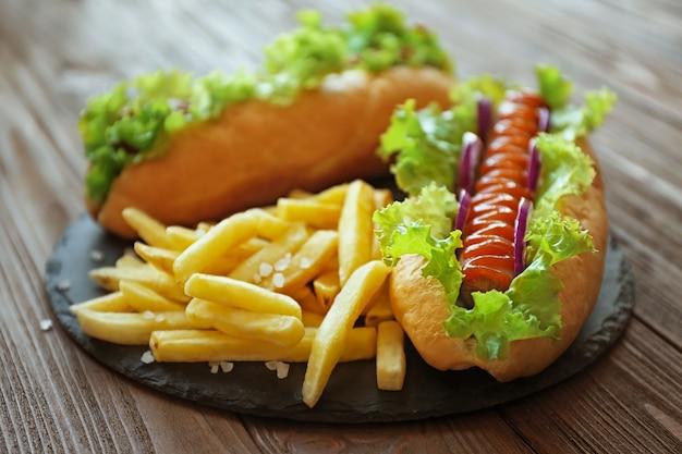 Deliziosi hot dog e patatine fritte su tavola di legno rotonda