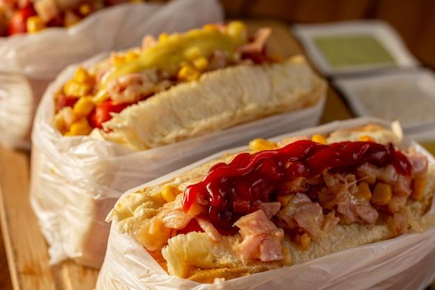 Delizioso hot dog con ingredienti e su sfondo colorato o in legno