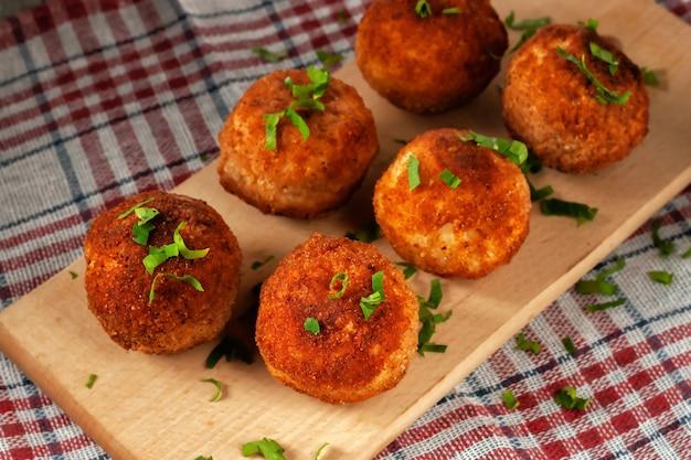 Arancini italiani caldi deliziosi - polpette di riso ripiene di formaggio su una tavola su un vecchio tavolo di legno