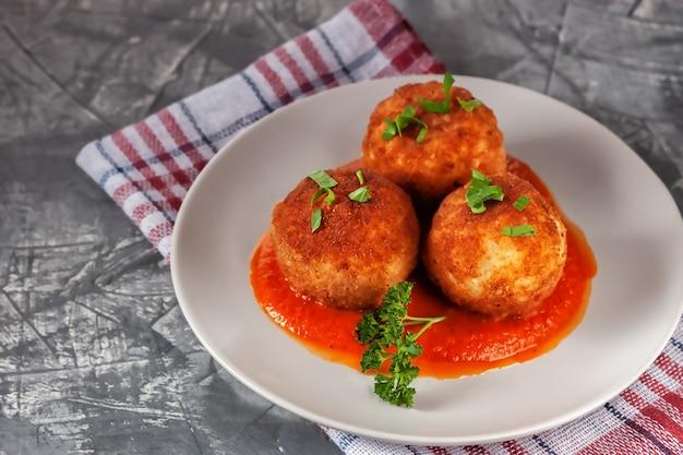 Deliziosi arancini italiani caldi - polpette di riso ripiene di formaggio in salsa di pomodoro, in un piatto su un vecchio tavolo di legno