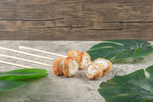 Deliziosi rotoli di sushi caldi e bacchette sulla superficie di pietra.