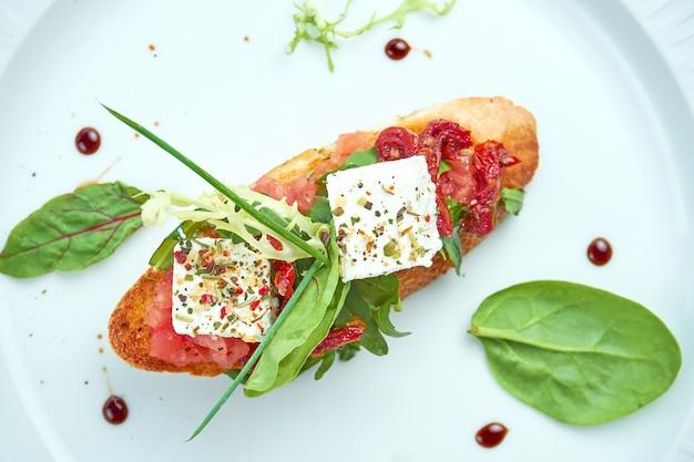 Deliziosa bruschetta italiana con formaggio feta e pomodori secchi su baguette bianca, servita in un piatto bianco sulla tovaglia bianca