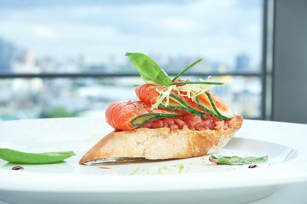Deliziosa bruschetta italiana con salmone, cetriolo su baguette bianca, servita in un piatto bianco sulla tovaglia bianca