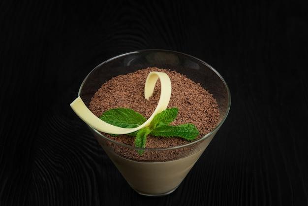 Delizioso tiramisù da dessert italiano su uno sfondo di legno nero decorato con foglia di menta con copia s...