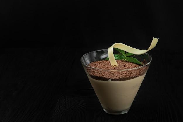 Delizioso tiramisù da dessert italiano, su uno sfondo di legno nero decorato con foglia di menta, con spazio di copia.