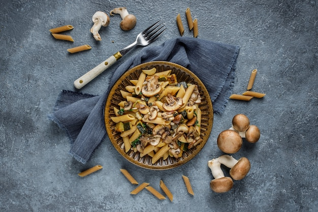 Piatto italiano delizioso, pasta di penne con spanach, zucchine e funghi arrostiti con aglio sul tavolo strutturato in marmo blu. pasta integrale e funghi champignon interi