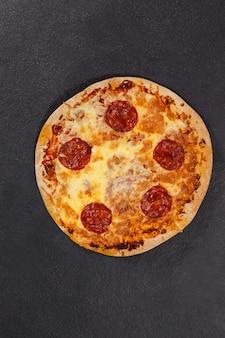 Pizza italiana deliziosa servita su sfondo grigio