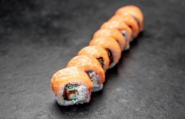Deliziosi rotoli di sushi giapponese su uno sfondo di pietra pronti da mangiare