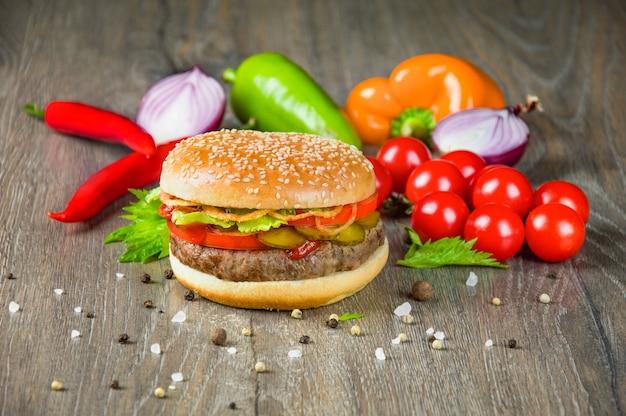 Delizioso hamburger succoso con pomodori freschi, peperoni ed erbe aromatiche