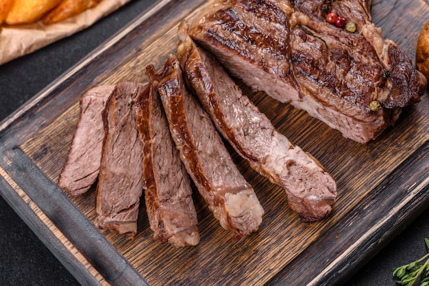 Deliziosa e succosa bistecca di manzo fresca con spezie ed erbe aromatiche su uno sfondo di cemento scuro. piatti alla griglia