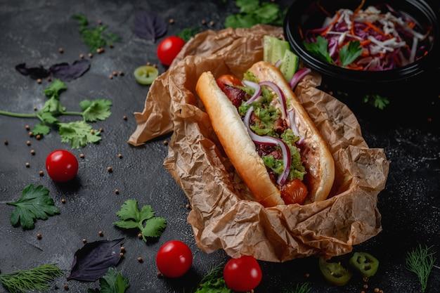 Delizioso e succoso hot dog con salsa di formaggio, pomodoro ed erbe fresche in assortimento, panino nel menu di un ristorante fast food su un tavolo di pietra scura. opzione salutare di fast food.