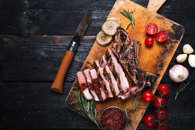 Un delizioso e succoso pezzo di carne alla griglia, verdure in tavola, una deliziosa cena per tutta la famiglia. fonte di colesterolo grasso e ipercalorico