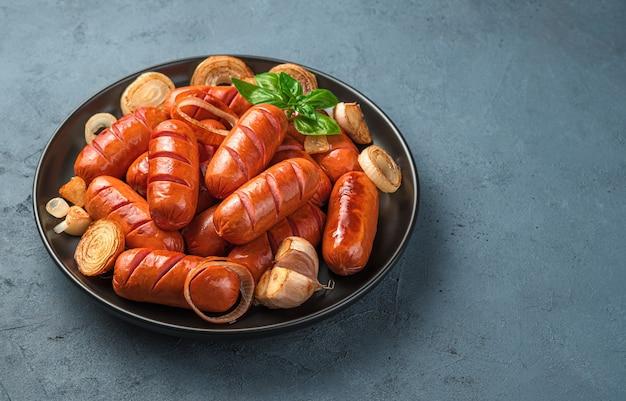 Salsicce deliziose e succose con aglio e cipolle in un piatto nero su uno sfondo grigio-blu. vista laterale, copia spazio