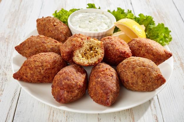 Deliziosi kibbeh ripieni di ragù di manzo fritto e pinoli serviti su un piatto bianco con lattuga e fette di limone sul vecchio tavolo di legno, ricetta libanese classica, vista orizzontale dall'alto, primo piano