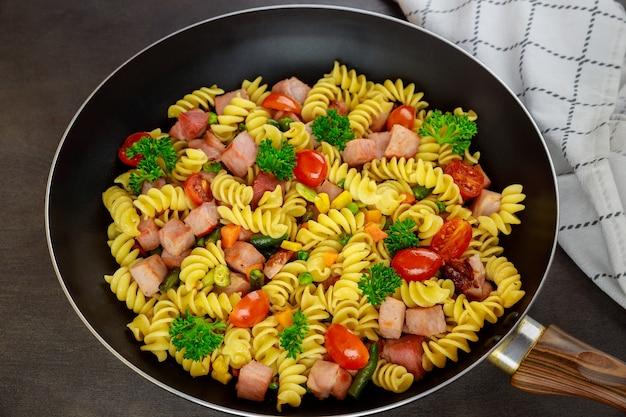 Deliziosi maccheroni con verdure e prosciutto tagliato. avvicinamento.