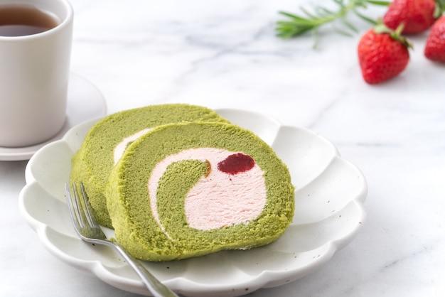 Deliziose fette di torta matcha swiss roll con gelato alla fragola su sfondo bianco, primo piano.