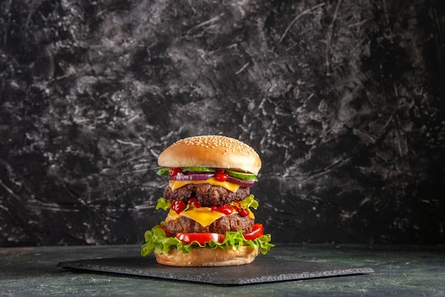 Delizioso panino di carne con pomodori verdi su vassoio di colore scuro su superficie nera