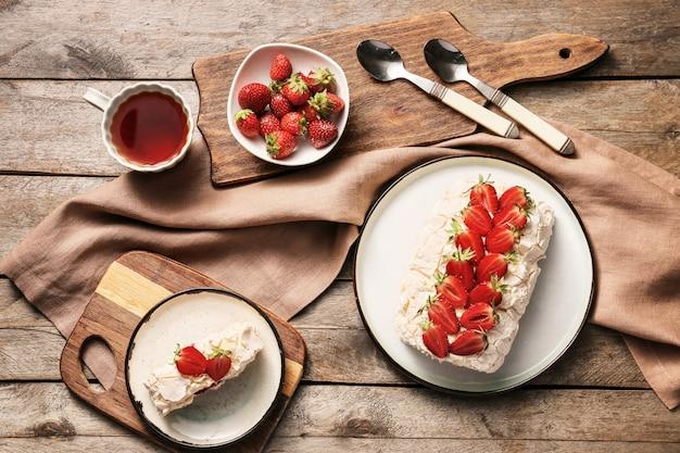 Delizioso rotolo di meringa con fragole e tè sul tavolo