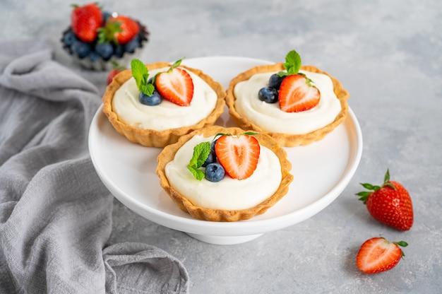 Deliziose mini crostate con frutti di bosco freschi e crema pasticcera su un piatto bianco su fondo grigio cemento. copia spazio.