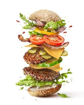 Hamburger mostro delizioso con ingredienti volanti isolati su bianco