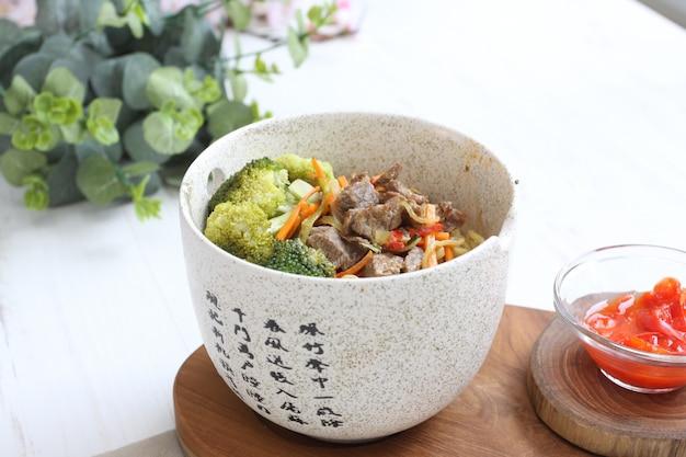 Deliziosi noodles con carne di manzo e broccoli sulla ciotola di marmo con salsa