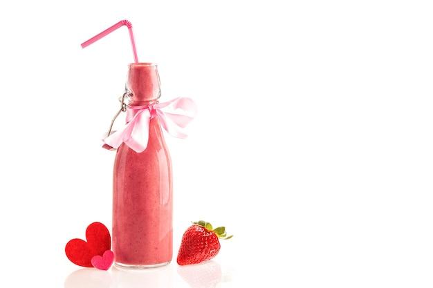 Frullato delizioso e nutriente a base di fragole fresche in una bottiglia di vetro con cannuccia, fiocco rosa e cuori di stoffa. regalo da regalare e condividere agli innamorati a san valentino. sfondo bianco.