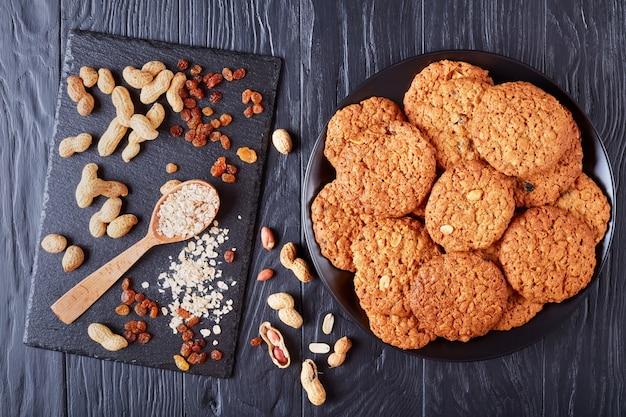 Deliziosa farina d'avena uvetta e biscotti di arachidi su una piastra nera con ingredienti su un vassoio di ardesia sullo sfondo, vista orizzontale dall'alto, laici piatta