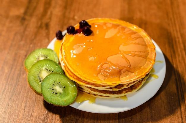 Deliziose frittelle con miele, kiwi e frutti di bosco.