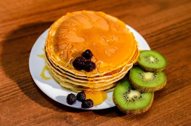 Deliziose frittelle con miele, kiwi e frutti di bosco