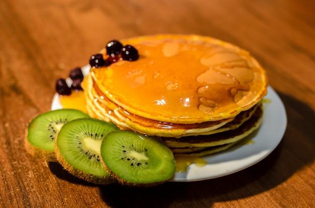 Deliziosi pancakes con miele, kiwi e frutti di bosco.