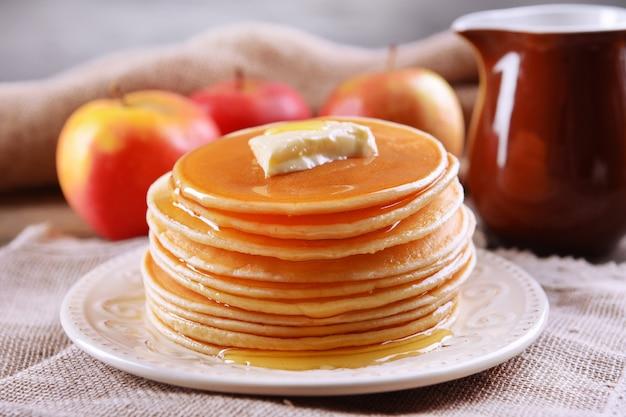 Deliziose frittelle con miele sulla piastra sul primo piano del tavolo