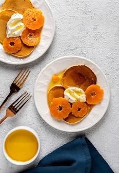 Deliziose frittelle con mandarini e miele o sciroppo d'acero per colazione su sfondo chiaro. copia spazio.