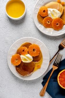 Deliziose frittelle con mandarini e miele o sciroppo d'acero per colazione su sfondo chiaro.