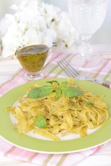 Deliziosa pasta al pesto sulla piastra sul tavolo sulla luce