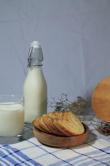 Deliziosa pasticceria su un piatto di legno con bottiglia di latte