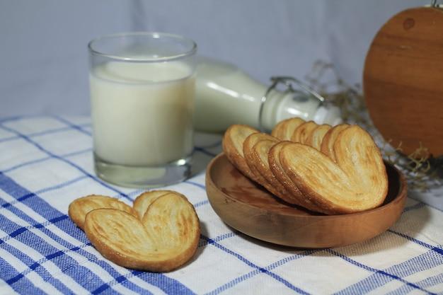 Deliziosa pasticceria su un piatto di legno con un bicchiere di latte