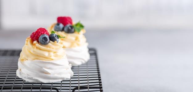Deliziosa torta pavlova con panna montata e frutti di bosco freschi sulla griglia di raffreddamento.